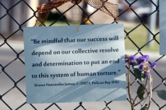 Photo of the sign on the gate at Corcoran during the hunger sitrke of 2013 with text of Sitawa: Be mindful that our success will depend on our collective resolve and determination to put an end to this system of human torture - Sitawa Nantambu Jamaa